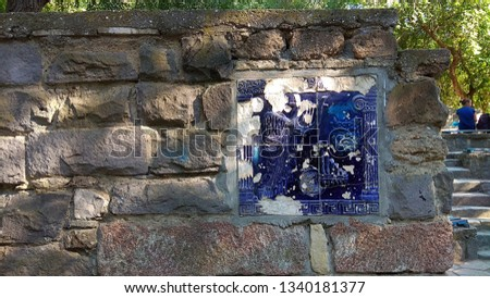 Vandalized theatre bas-relief tile on a stone fence wall, imitating the ancient ruins in a park for children. Stone relief depicting the ancient Greek Dionysius mask,lyre,panpipes,musician,columns.