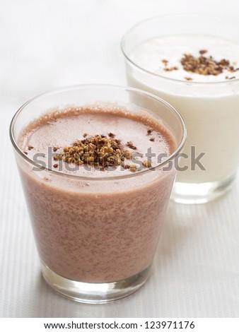 Vanilla and chocolate milkshakes in glass, selective focus
