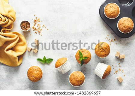 Vanilla Caramel Muffins In Paper Cups On Grey Concrete Background. Table Top View. Copy Space For Text Photo stock ©