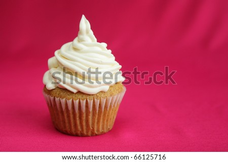 Vanilla cup cake with white icing on red background