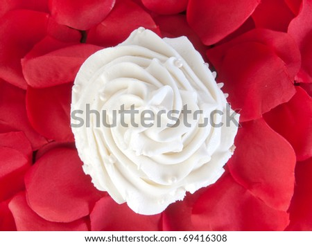 vanilla cupcake surrounded by rose petals