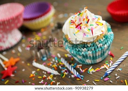 Vanilla cupcake with candles, paper and candies on a wooden table