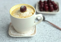 vanilla cupcake with cherries in a mug. Easy microwave cooking concept. The muffin is decorated with fresh cherries. White cup on a light background. Delicious sweet dessert. High quality photo