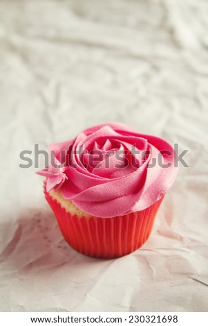 Vanilla cupcake with pink rose piping icing and clear space for text