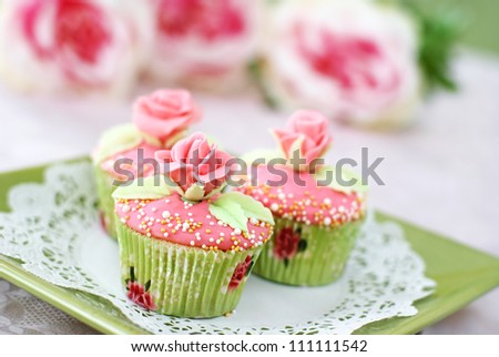 Vanilla cupcakes with pink frosting decorated with pearls and roses made of fondant.