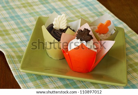 Vanilla cupcakes with vanilla, chocolate, and mocha frosting, decorated with chocolate leaves