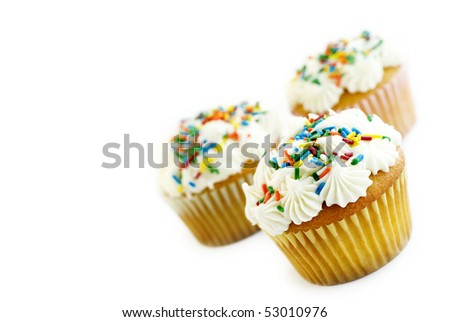 Vanilla Cupcakes with white frosting and colored sprinkles tilted in corner with selective focus, isolated on white background with copy space