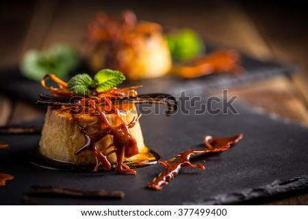 Vanilla flan dessert served on black slate