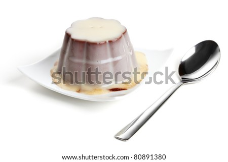 Vanilla garnished chocolate pudding with spoon on white background