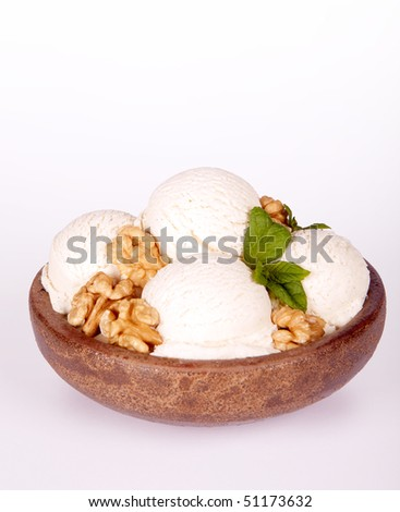 Vanilla ice cream bowl with fresh walnuts