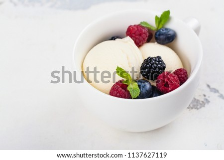 Vanilla ice cream scoops with fresh raspberry and blueberry on white background