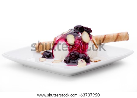 Vanilla ice cream topped with blueberry sauce and almonds, with wafer cookie roll.