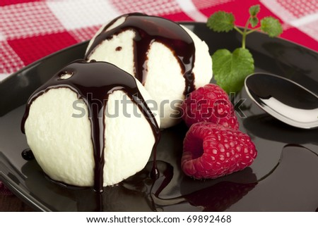 vanilla ice cream with chocolate topping, raspberries and mint garnish