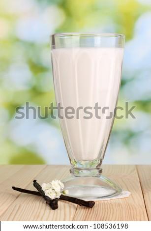 Vanilla milk shake on wooden table on bright background