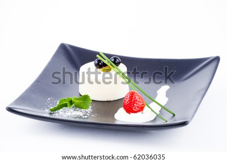 Vanilla mousse dessert on square black plate with cranberries