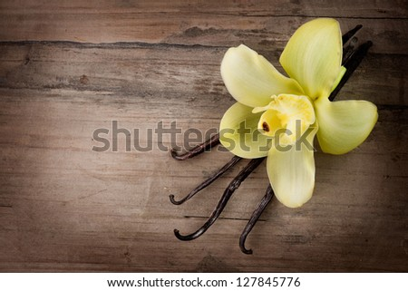Vanilla Pods and Flower over Wooden Background. Vanilla Pod Stick