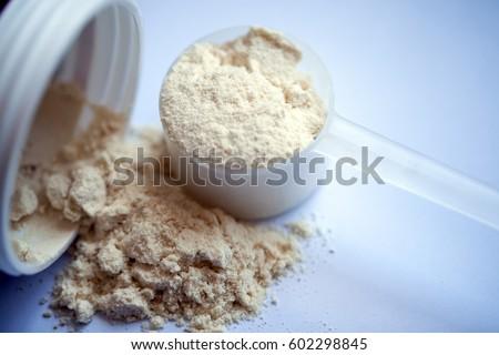 Vanilla protein powder in scoop on white background