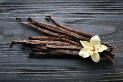 Vanilla sticks and flower on wooden background