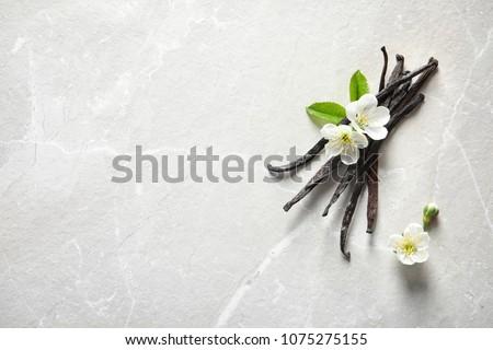 Vanilla sticks and flowers on light background