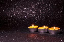 Vanilla white burning candles on black dark bokeh background, soft light. Muslim community holy month Ramadan Kareem. Greeting Festive card. Copy space. Candle making. Low key photo