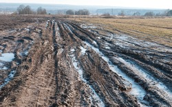 Vanishing dirty road through fallow field with mud and puddles at early spring