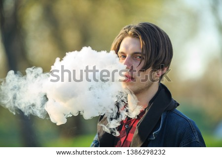Vape teenager. Portrait of young handsome guy smoking an electronic cigarette  outdoors in a park in spring. Bad habit that is harmful to health. Vaping activity.