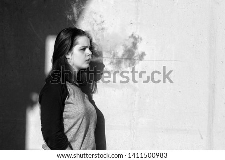 Vape teenager. Young cute girl in  casual clothes smokes an electronic cigarette near the wall outdoors in summer day. Bad habit that is harmful to health. Vaping activity. Black and white. Close up. #1411500983