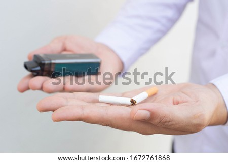 Vaping device and cigarettes in the man's hand, Man offers a choice between tobacco cigarette and electronic cigarette, concept of choosing the type of cigarette