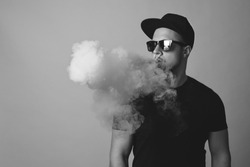 Vaping man. A cloud of vapor. red background.