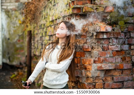 Vaping teenager. Young pretty white caucasian teenage girl with problem skin smoking an electronic cigarette the ruined brick wall on the street in the autumn. Bad habit. Vape activity. #1550930006