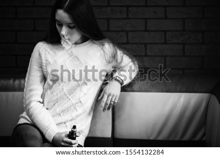 Vaping teenager. Young pretty white caucasian teenage girl with problem skin smoking an electronic cigarette indoors. Life-threatening bad habit. Vape activity. Black and white. Black and white #1554132284