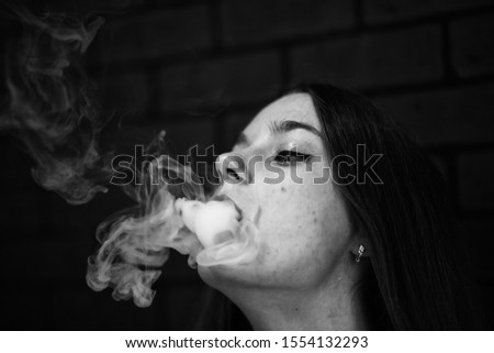 Vaping teenager. Young pretty white caucasian teenage girl with problem skin smoking an electronic cigarette indoors. Life-threatening bad habit. Vape activity. Black and white. Black and white #1554132293