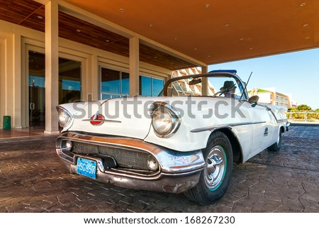 VARADERO, CUBA - APRIL 24: Old american car standing near hotel entrance with man in hat sitting inside shown on 24 April 2008 in Varadero, Cuba