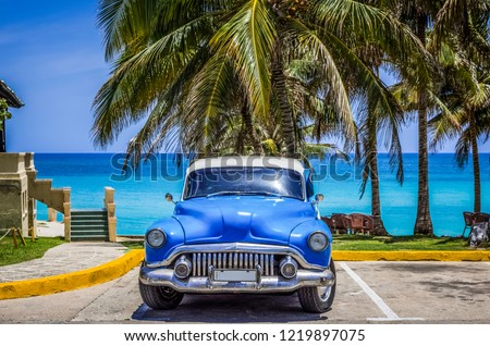 Varadero, Cuba - June 21, 2017: HDR - American blue Buick classic car parked under palms on the beach in Varadero Cuba -Serie Cuba Reportage #1219897075