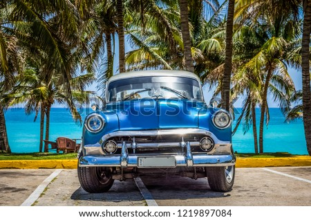 Varadero, Cuba - June 21, 2017: HDR - American blue Buick classic car with white roof parked under palms in Varadero Cuba - Serie Cuba Reportage #1219897084