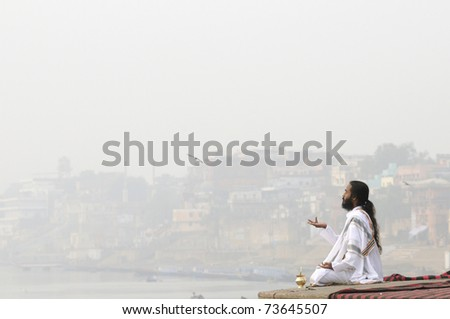 VARANASI - DECEMBER 31: A monk worshiping  mother Ganges on a foggy morning  on the ghats of Varanasi - the cultural capital of the Hindus , in Varanasi, India on December 31, 2010.
