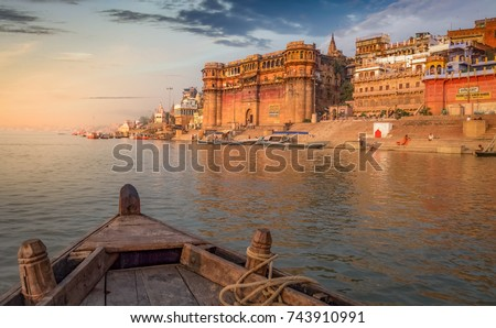 Varanasi Ganges river ghat with ancient architectural buildings and temples as viewed from a boat on the river at sunset.