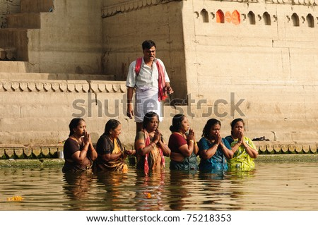 VARANASI, INDIA - APRIL 1: An Unidentified Hindu priest dictates prayer to women pilgrims as they pray on holy Ganges river at the  Ramnavami festival on April 1, 2011 at Varanasi, Uttar Pradesh, India.