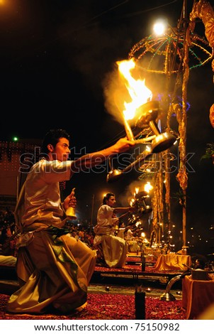 VARANASI, INDIA - APRIL 1: Unidentified priests perform fire ritual during religious Ganga Aarti on April 1, 2011 at Varanasi, Uttar Pradesh, Central India. Seven priests are involved in this prayer.