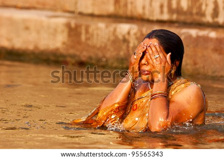 VARANASI, INDIA - APRIL 25: Unidentified woman washes her face in the ...