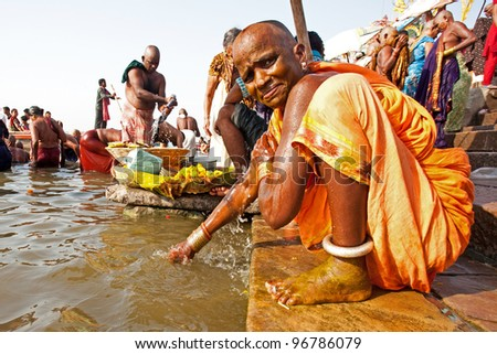 VARANASI, INDIA - APRIL 23: Unidentified woman washing herself in the river Ganga on April 23, 2011 in the holy city of Varanasi, India. The holy ritual of washing is held every day.