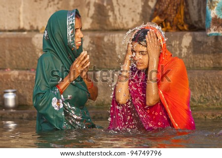 VARANASI, INDIA - APRIL 24: Unidentified women wash themselves in the river Ganga on April 24, 2011 in the holy city of Varanasi, India. The holy ritual of washing is held every day.