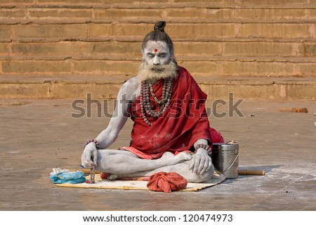 VARANASI INDIA DEC 1 An unidentified naga baba sadhu sits on the ghat along the Ganges on December 1 2012 in Varanasi India Tourism has drawn many alleged fake sadhus to Varanasi
