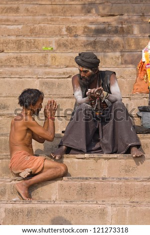 VARANASI, INDIA - DECEMBER 1: An unidentified sadhu and men sits on the ghat along the Ganges on December 1, 2012 in Varanasi, India. Tourism has drawn many alleged fake sadhus to Varanasi
