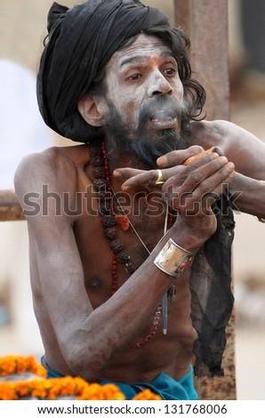 VARANASI, INDIA - FEBRUARY 20: A shaiva sadhu smokes pot during prayer on the auspicious Maha Shivaratri festival on February 20, 2012 at Varanasi, Uttar Pradesh, India.
