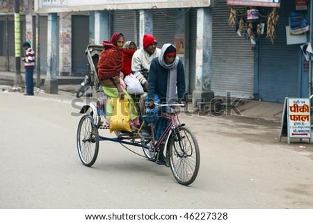 VARANASI, INDIA - JANUARY 2: People on rickshaw January 2, 2010 in Varanasi, India. The rickshaw is the most widely used means of transport in India.