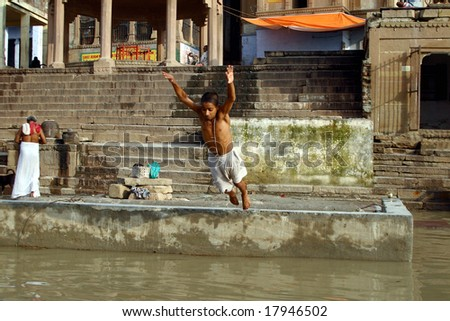 VARANASI, INDIA - 10 JULY: A young adult jumps into the water during a religious ceremony at Uttar Pradesh on July 10, 2007 in Varanasi, India.