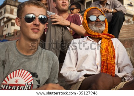 VARANASI, INDIA - JULY 22: Indian man and western tourist watch solar eclipse together, wearing dark glasses July 22, 2009 in Varanasi, India.