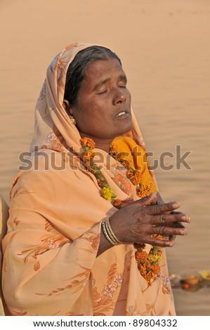 VARANASI, INDIA - NOVEMBER 21: An unidentified woman prays near Ganges on November 21, 2010 in Varanasi, Uttar Pradesh, India. Hindus believe that bathing in the Ganges remits sins.