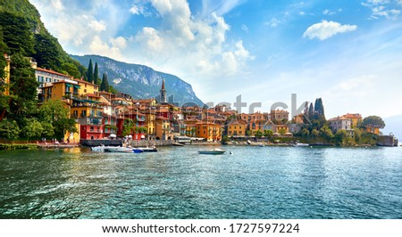 Varenna, Italy. Picturesque town at lake Como. Colourful motley Mediterranean houses at stone beach coastline among green trees. Popular health resort and touristic location. Summer day landscape. Foto stock ©